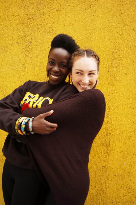 Two young women, one black, one white, hugging each other and smiling