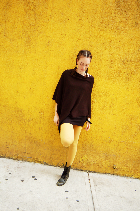 Young white woman leaning against a yellow stucco wall