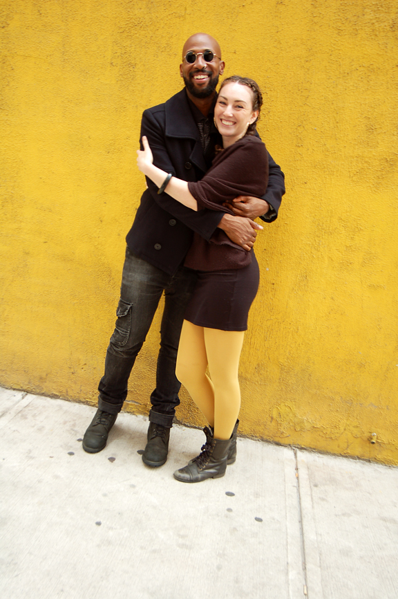 Young black man and young white woman hugging each other and smiling, standing in front of yellow stucco wall