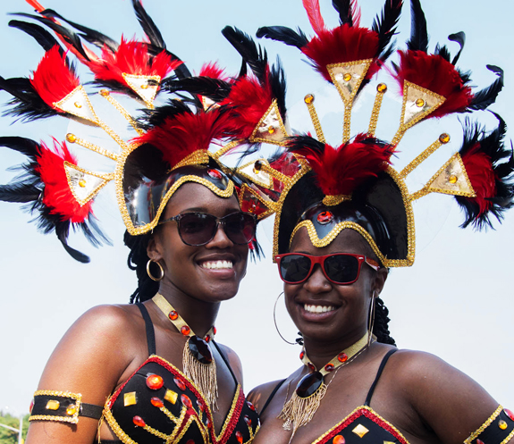 Two women dressed up for Caribbean carnival outfits with feathers