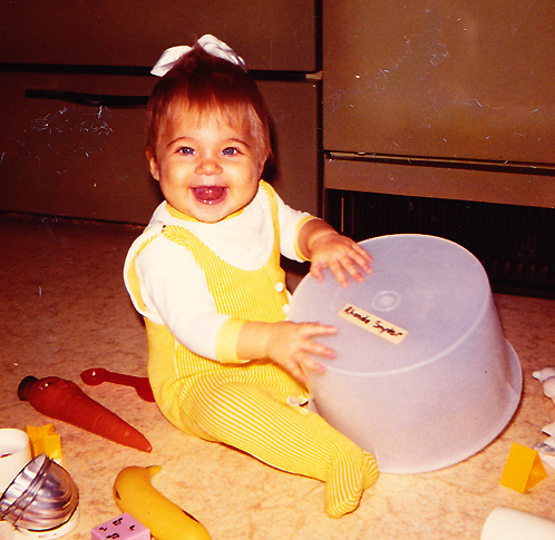 Female toddler in yellow outfit playing on floor with plastic container.