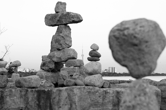 Piles of rocks balancing percariously on beach front with urban city scape and CN Tower in the background