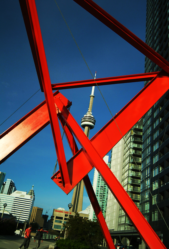 Orange metal angular sculpture framing a backdrop with the CN Tower, buildings and blue sky