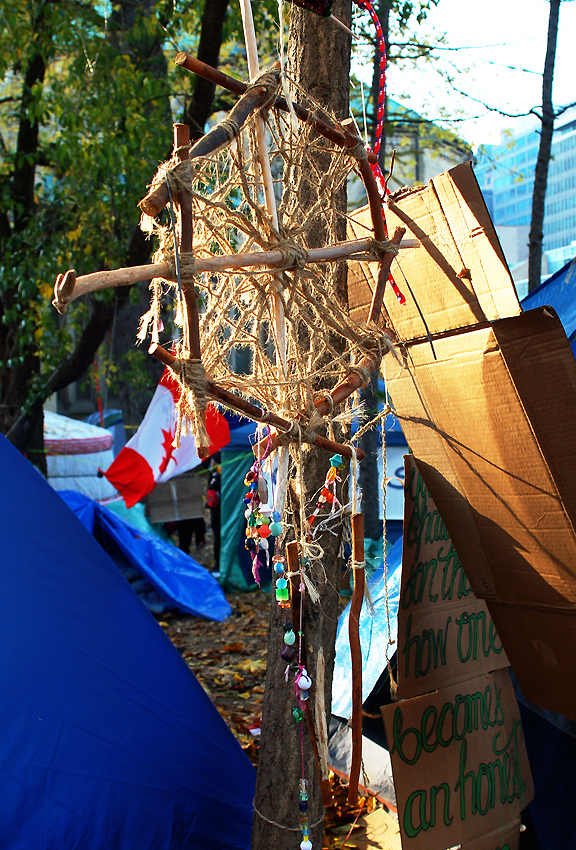 Dream catcher made of twigs and string hung between tents at Occupy Toronto, sun shining and Canadian Flag behind it