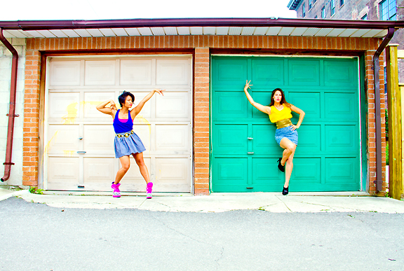 Two female dancers posing in front of old garage doors in alley.