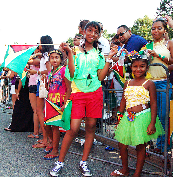 Three little girls with the flag of Guyana.