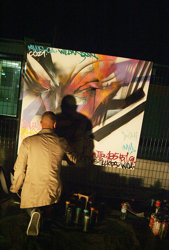 bald man kneeling while painting a canvas outside at night in graffiti style with spray paint
