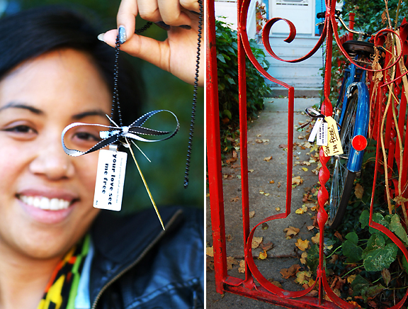 Jewellery designer, Sas Reyes, about to hang her last necklace on gate in Kensington Market, Toronto.