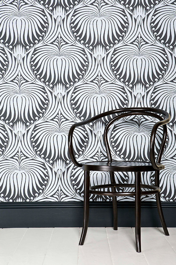 Black and white graphic print wallpaper with black bentwood chair in front.