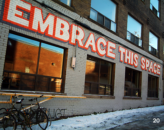 Brick wall with painting across the side with the words Embrace this Space