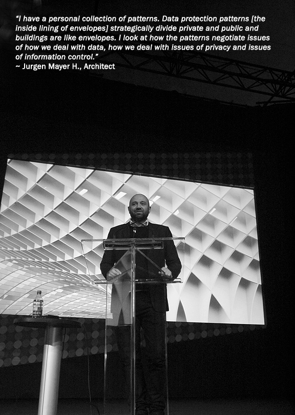 Architect Jurgen Mayer H. speaking at podium with image of his architecture behind him.