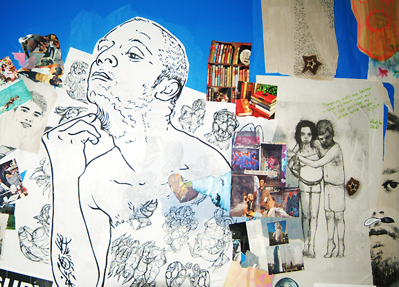 Pieces of paper and printed photographs pasted to blue wall