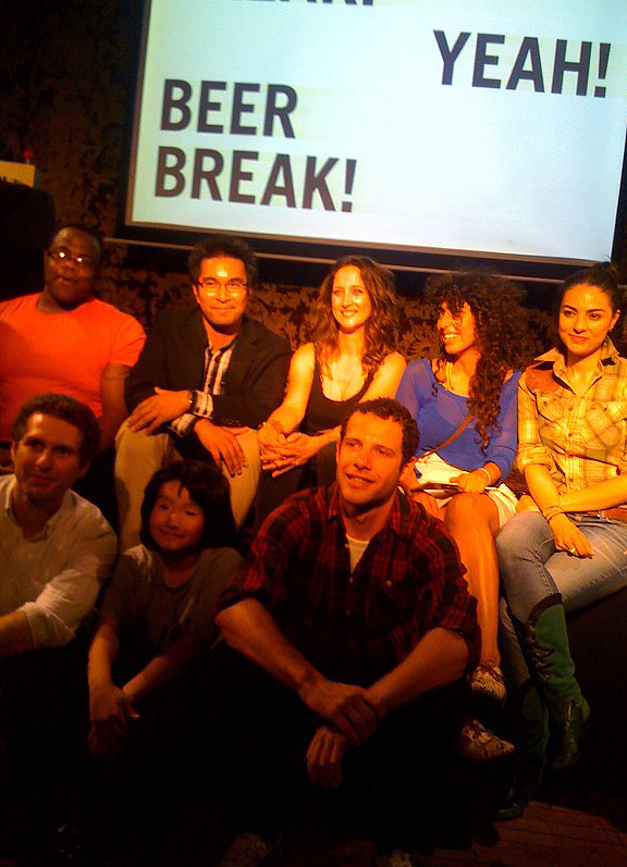 Group of people sitting on a stage in front of screen that says Yay Beer Break