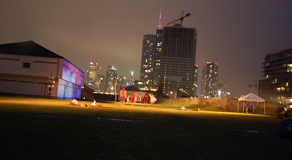 Aboriginal dance troupe performing outside on hills at night with city of Toronto as backdrop