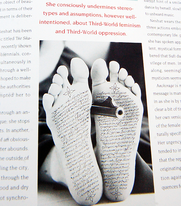 Photograph on page of magazine with woman holding a gun between her feet and Farsi script written on the bottom of them.