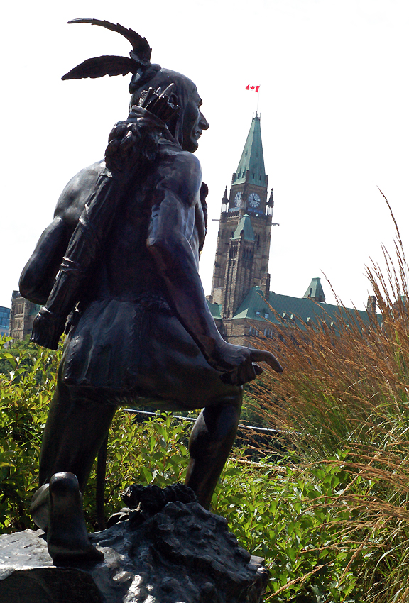 Metal sculpture of native man in traditional attire kneeling with quills. Canada's Parliament Buildings in the background.