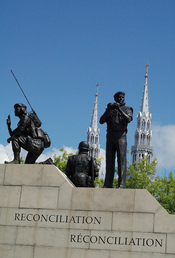 Metal sculpture of two men and a woman in armed forces attire with words reconcilation underneath them and antique church spires behind them.