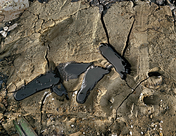 Image of a man's footprints solidified in sand with oil pooling into them.