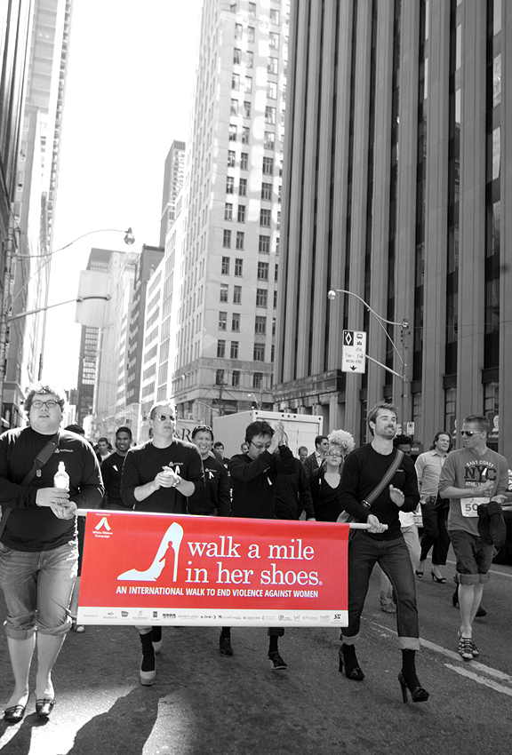 Men in high heel shoes holding banner saying Walk a Mile in Her Shoes