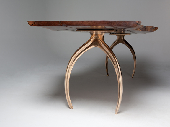 wood table with metal bases shaped like wishbones