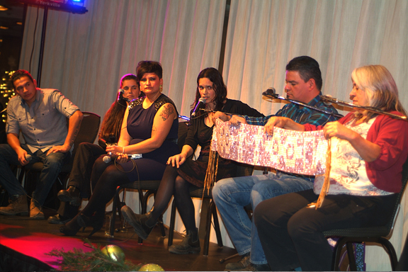 Woman speaking and holding beaded wampum belt with other panelists