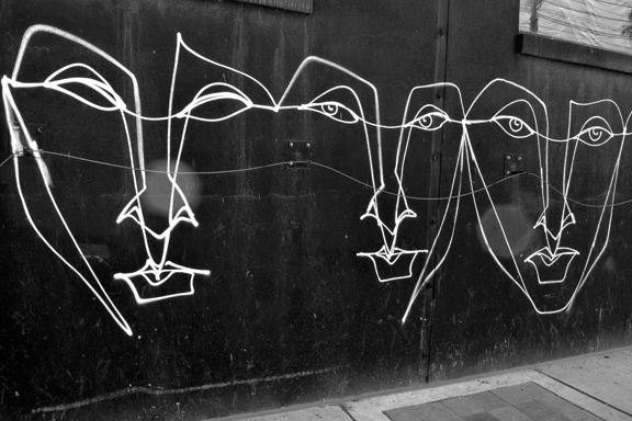 Black grafitti wall with faces outlined in white