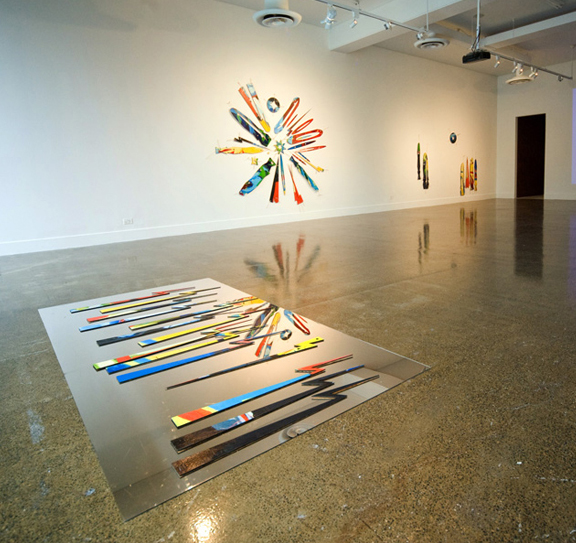 Asbtract wood pieces assembled on the wall of a gallery and on the floor on a mirror