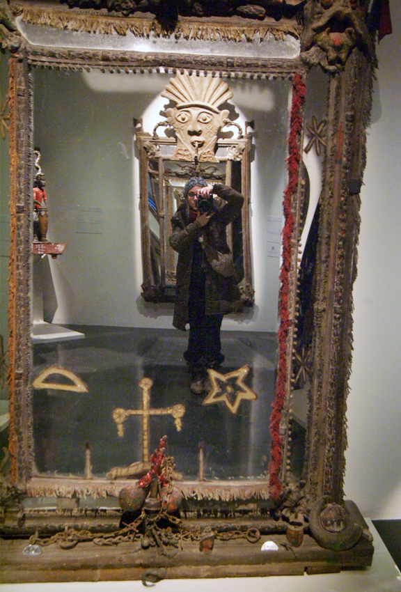 woman with camera looking into large mirror with series of mirrors reflecting in mirror