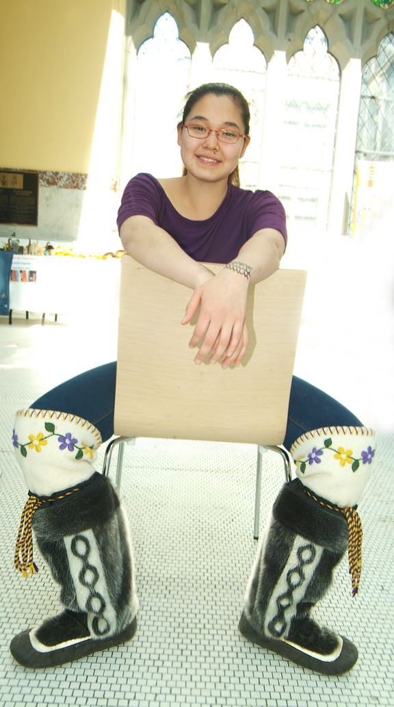 Young Inuk woman sitting on chair wearing mukluks