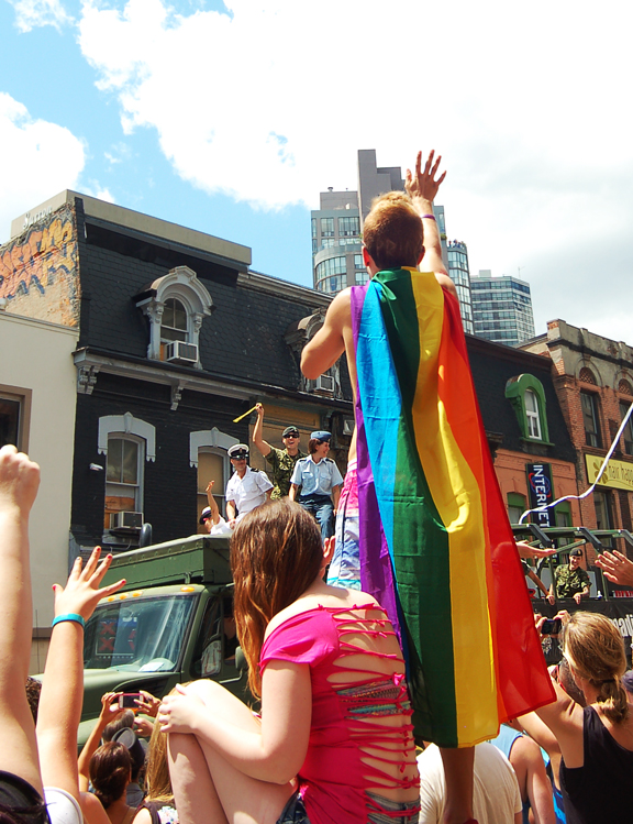 Young guy standing on garbage bin wearing pride flag and waving to a float