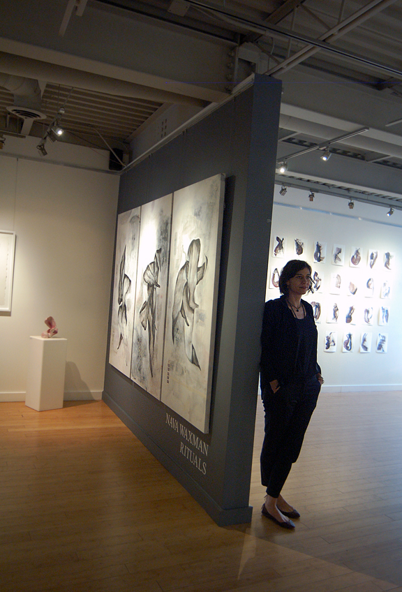 Woman standing at the corner of a gallery with her paintings and drawings behind her