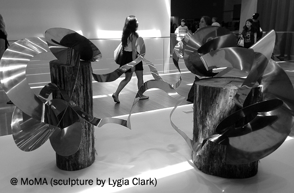 sculpture made out of rough wood posts and bent shiny metal, people walking by