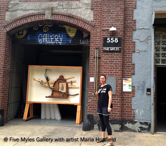 Woman standing in front of a brick facade gallery with the address and sign that says Five Myles