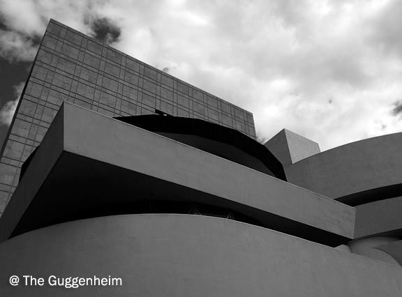 The modern architecture of the Guggenheim Museum against the sky with clouds