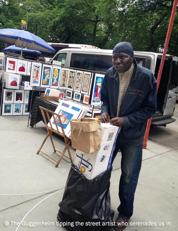 Black man busking in front of street side display of paintings