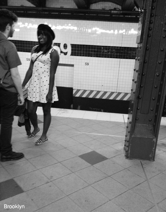 Young black woman laughing and talking to young white man with beard, standing in a subway station