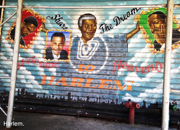 Painting on a metal pull down door with mural of Malcolm X, Obama, Nelson Mandela and Martin Luther King. Reads Share the Dream, Welcome to Heavenly Harlem
