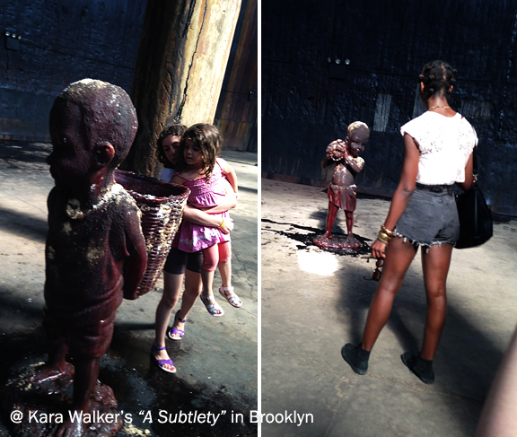 Little girl picking up another little girl to look in basket of a sculpture of a child. Black woman looking at the sculpture of a black child labourer