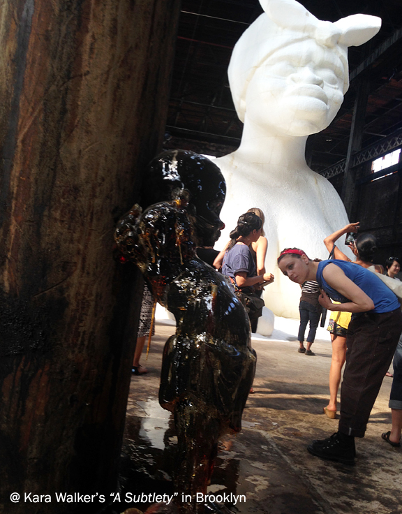 Large white sculpture of a black woman with a handkerchief wrap on head, people standing looking at the sculpture