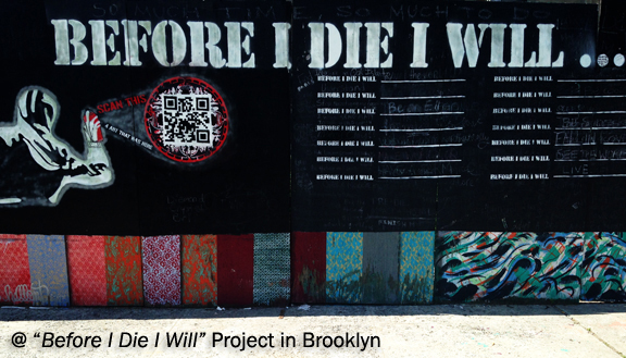 Street art project with words Before I Die I Will painted with chalkboard paint and peoples answers scribbled in chalk