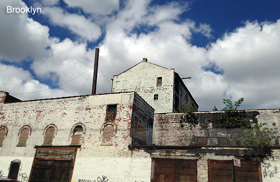 Old white brick building boarded up against blue sky full of clouds