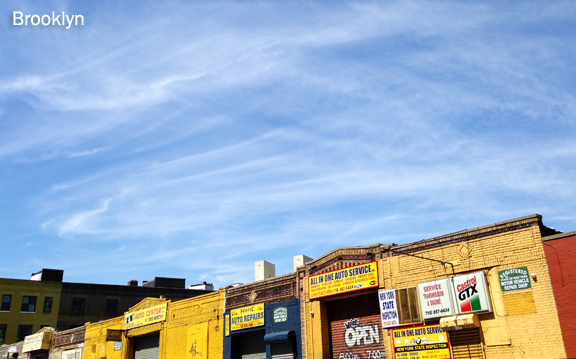 One story high brick industrial buildings painted in yellow and other bright colours against a blue sky