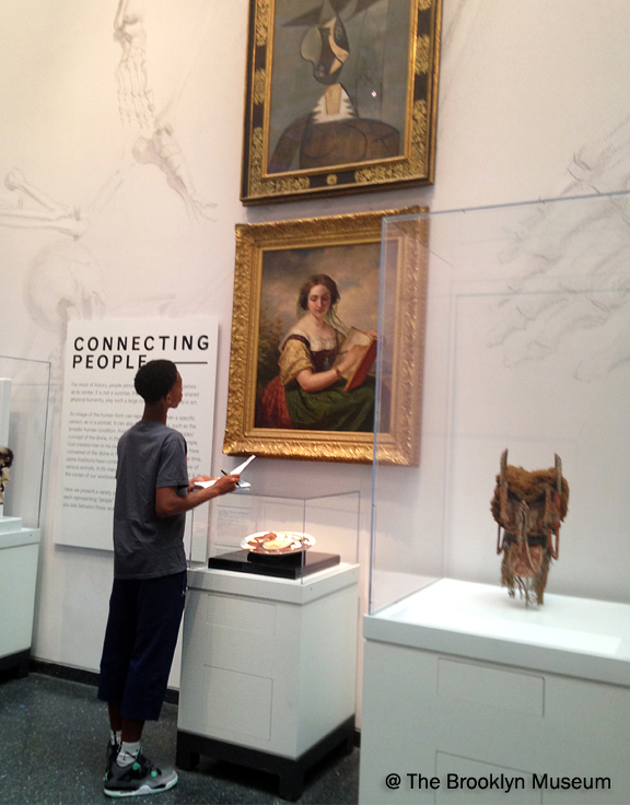 Young black boy with notepad and pencil looking up at classic European painting of a white woman