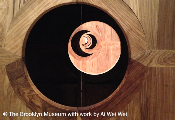 close up shot of wood paneled structure with holes that show other structures behind it. The shape repeats a crescent moon
