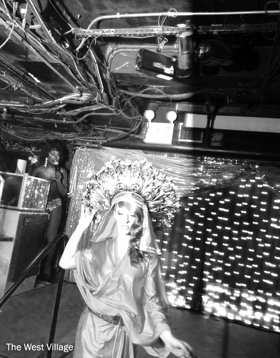 Drag show in nightclub, white queen descending the stairs with black queen in back with microphone