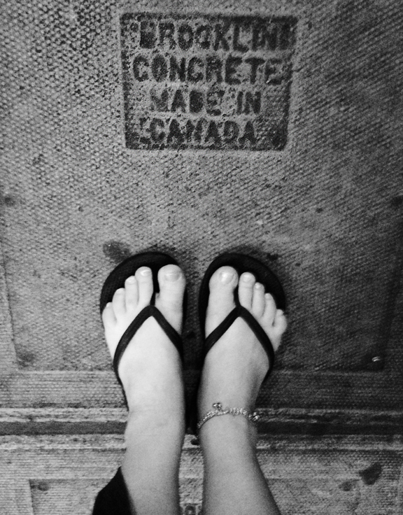 Woman's feet in sandals standing on concrete slab that reads Brooklyn Concrete Made In Canada
