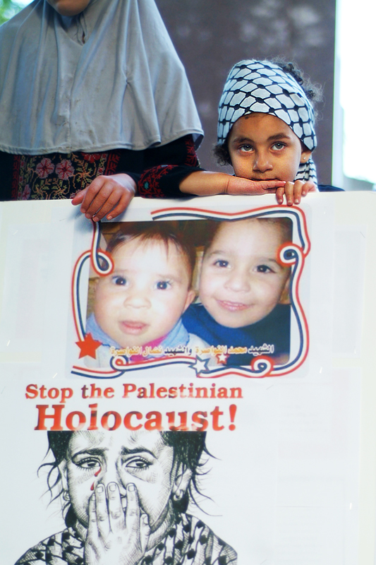 Little Palestinian girl rests her arms on poster with images of the children killed. The poster reads Stop the Palestinian Holocaust