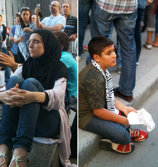 Young woman sits on steps and listens, crowds surround her in the background. Young boy with keffiyeh around his neck and Nike shoes sits on the sidewalk while adults stand around him