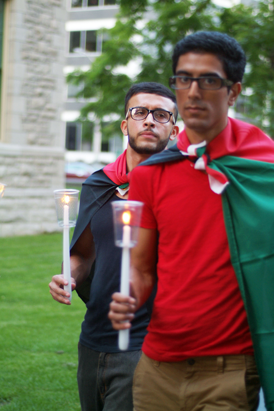 Two young men wearing Palestinian flags like capes walk with candles in their hands