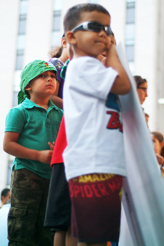 Little Palestinian boys hold posters, one little boy years sunglasses and Spiderman shorts